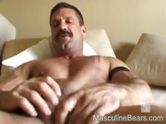 Strong hairy hands stroke a strong shaft